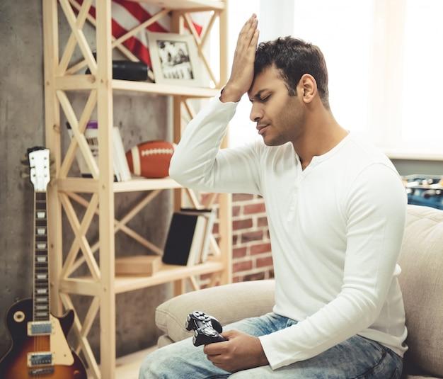 Afro americano está sentado chateado enquanto estiver jogando o jogo.