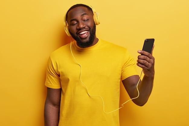 Afro-americano feliz gosta de cantar junto, segura um celular moderno conectado a fones de ouvido