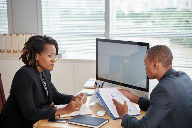 Afro-americano homem de terno segurando documentos e conversando com o chefe feminino