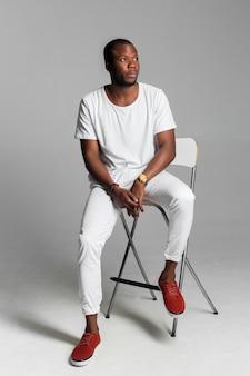 Afro-americano homem sentado em uma cadeira