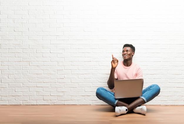 Afro americano homem sentado no chão com seu laptop apontando com o dedo indicador uma ótima idéia