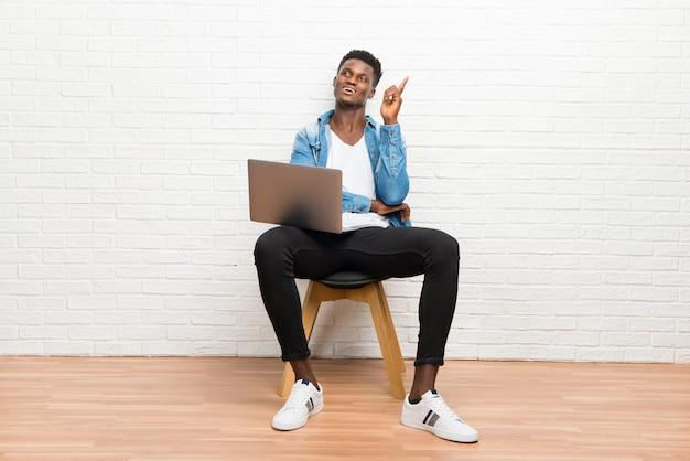 Afro americano homem trabalhando com seu laptop apontando com o dedo indicador uma ótima idéia