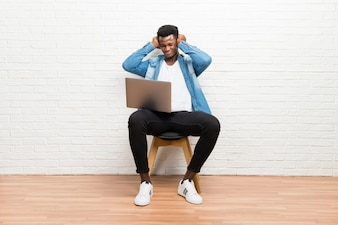 Afro americano homem trabalhando com seu laptop cobrindo ambas as orelhas com as mãos