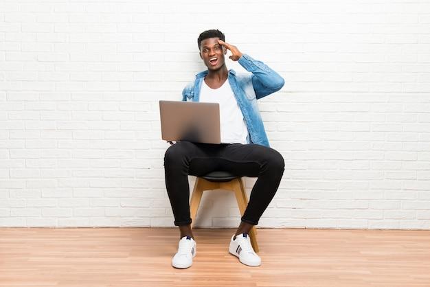 Afro americano homem trabalhando com seu laptop, com a intenção de perceber a solução