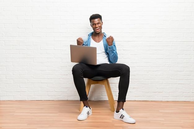 Afro americano homem trabalhando com seu laptop comemorando uma vitória
