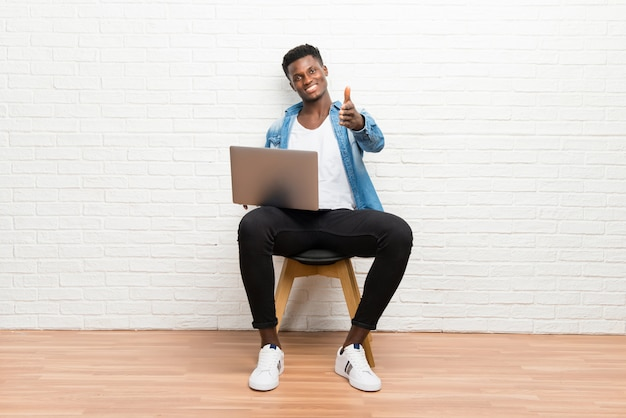 Afro americano homem trabalhando com seu laptop handshaking após bom negócio