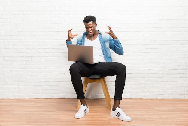 Afro americano homem trabalhando com seu laptop irritado com raiva no gesto furioso