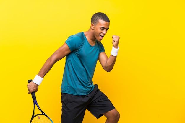 Afro americano jogador de tênis homem sobre amarelo isolado