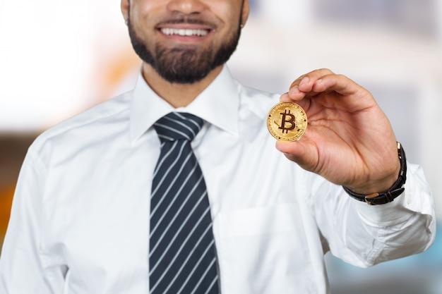 Afro americano jovem, com, bitcoin, em, mão