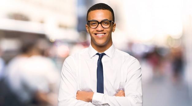 Afro americano jovem empresário com óculos e feliz na cidade