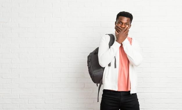 Afro americano jovem estudante cobrindo a boca com as duas mãos