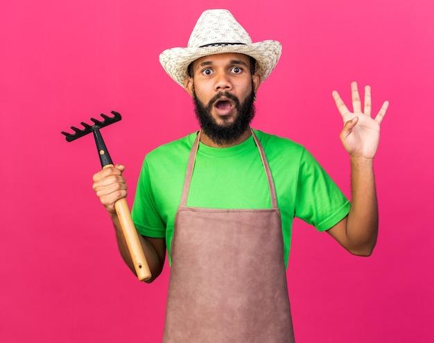 Afro-americano jovem jardineiro assustado com chapéu de jardinagem segurando o ancinho e mostrando quatro isolados na parede rosa
