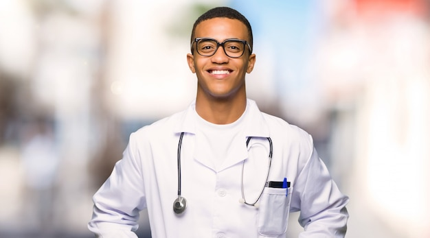 Afro americano jovem médico com óculos e feliz ao ar livre