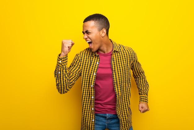 Afro-americano jovem na parede amarela feliz e pulando