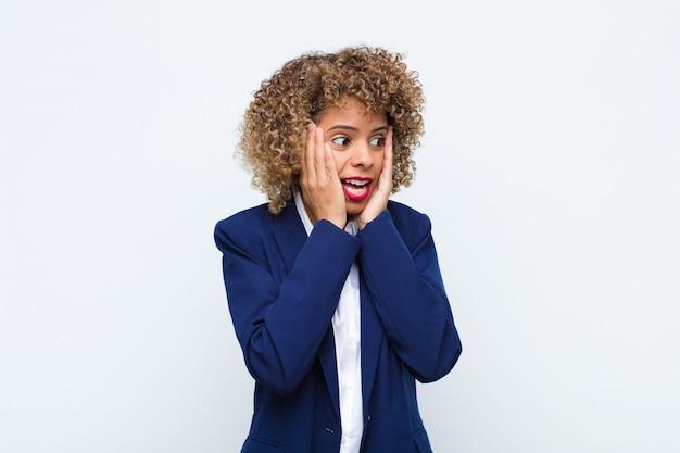 Afro-americano jovem, sentindo-se feliz, animado e surpreso, olhando para o lado com as duas mãos no rosto contra a parede plana