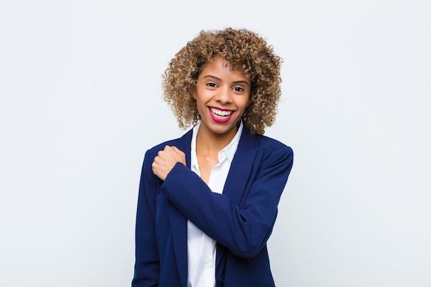 Afro-americano jovem, sentindo-se feliz, positivo e bem-sucedido, motivado quando enfrenta um desafio ou comemora bons resultados contra a parede plana