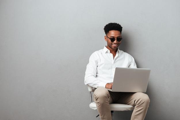 Afro-americano jovem sorridente usando computador portátil