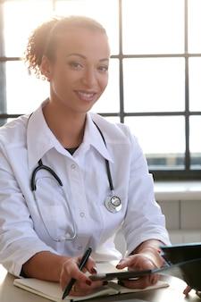 Afro-americano médico feminino posando, especialista em medicina
