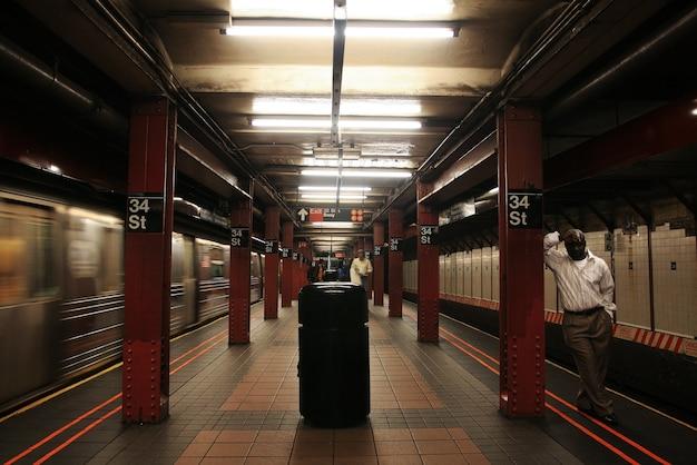 Afro-americano no 34º terminal do metrô de nova york espera pelo trem