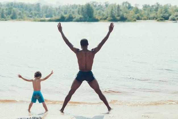 Afro-americano pai e filho está descansando na praia