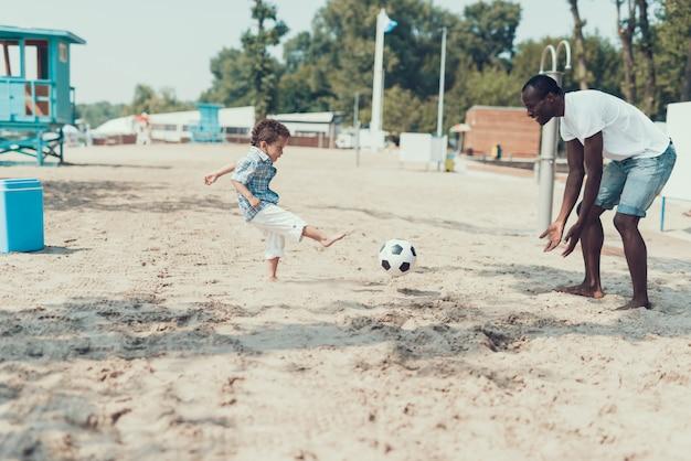 Afro-americano pai e filho estão jogando com bola de futebol