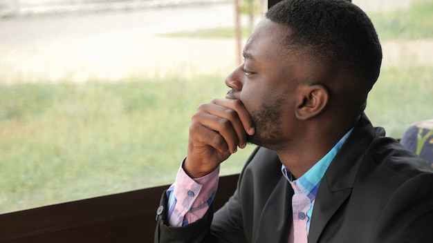 Afro americano pensativo cansado jovem empresário está sentado no café. retrato de jovem negro olha para a janela vira a cabeça e olha para a câmera. jovem barbudo usa camisa e paletó.