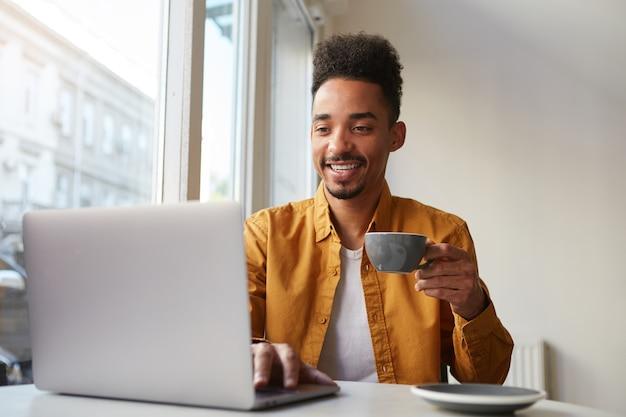 Afro-americano sentado à mesa em um café e trabalhando em um laptop, veste uma camisa amarela, bebe café aromático, conversando com a namorada, aproveita o dia.