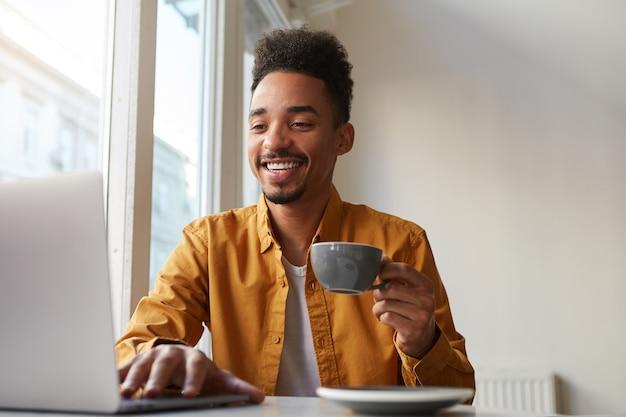 Afro-americano sentado à mesa em um café e trabalhando no laptop, veste uma camisa amarela, bebe um café aromático, se comunica com sua irmã que está longe de outro país, gosta do trabalho