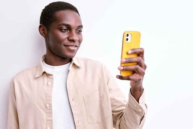 Afro-americano simpático segurando um smartphone nas mãos