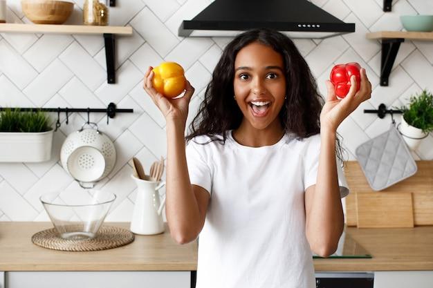 Afro bonita mulher sorridente detém dois pimenta