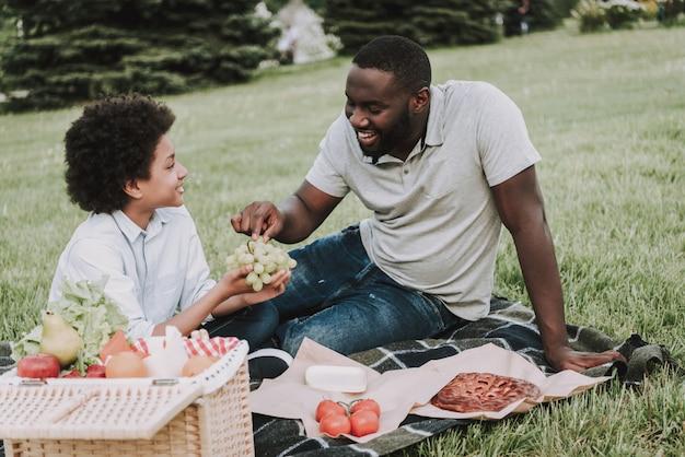 Afro boy detém uvas e pai afro stretches para tentar.