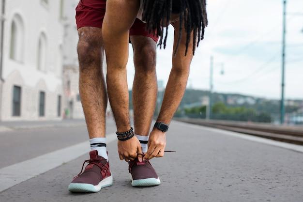 Afro cara amarrando os sapatos