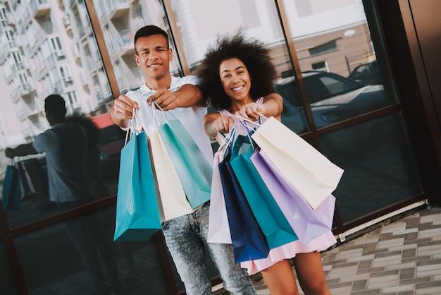Afro casal está mostrando sacolas de compras