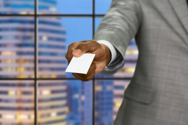 Afro empresário dá cartão de visita. cartão em branco sobre fundo de megalópole. corretor de imóveis na capital. lugar para sua publicidade.