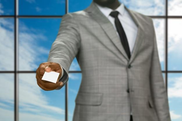 Afro empresário dando cartão de visita. homem apresentável no fundo do céu. aparecimento repentino do inspetor de segurança. visitante na sede da empresa.