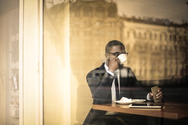 Afro empresário tomando um café