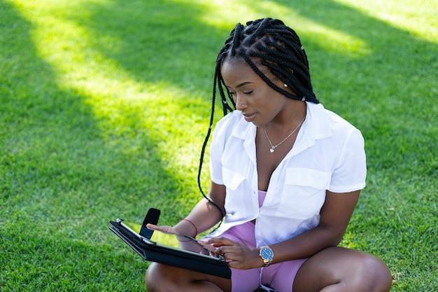 Afro estudante universitária sentada na grama do campus com um tablet digital.