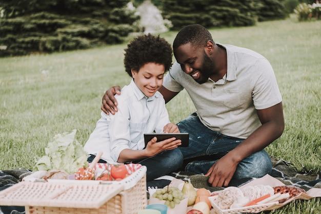 Afro filho e pai olhando no tablet no piquenique
