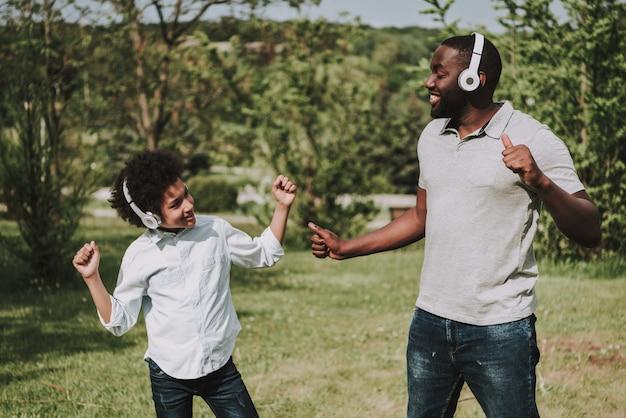 Afro filho e pai ouvem música e dança.