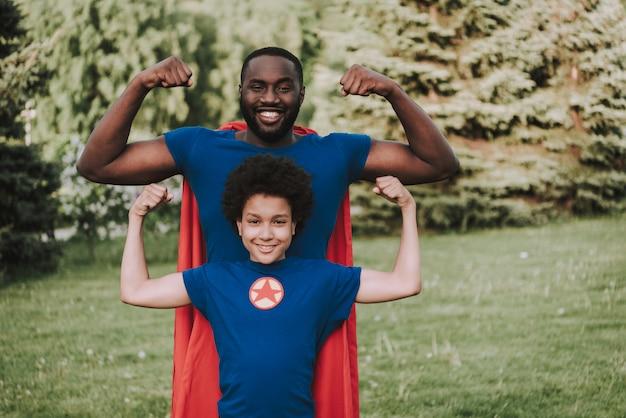 Afro filho e pai vestindo ternos de super-heróis