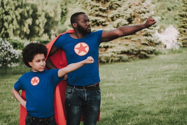 Afro filho e pai vestindo ternos de super-heróis.