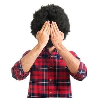 Afro homem cobrindo os olhos