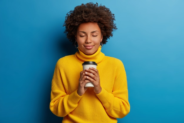 Afro jovem satisfeita adora bebida, segura café para viagem, fecha os olhos, usa suéter amarelo, isolado sobre fundo azul