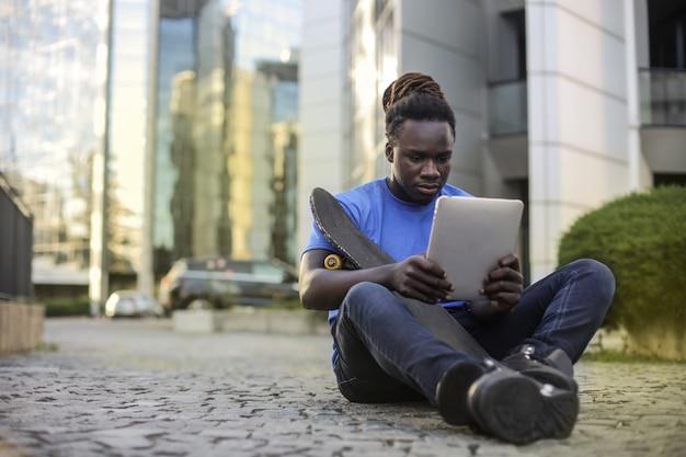 Afro jovem sentado na rua com um tablet