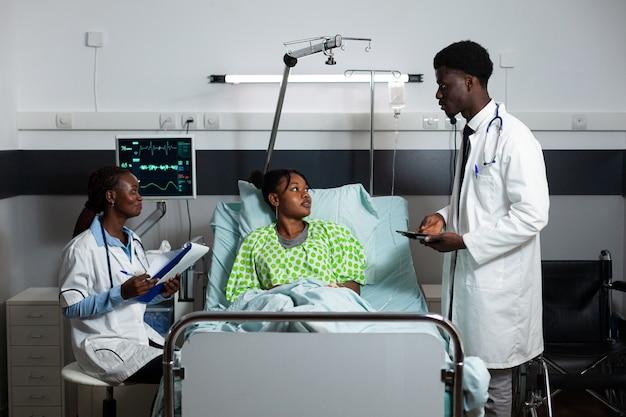 Afro médicos consultando um jovem adulto na enfermaria do hospital