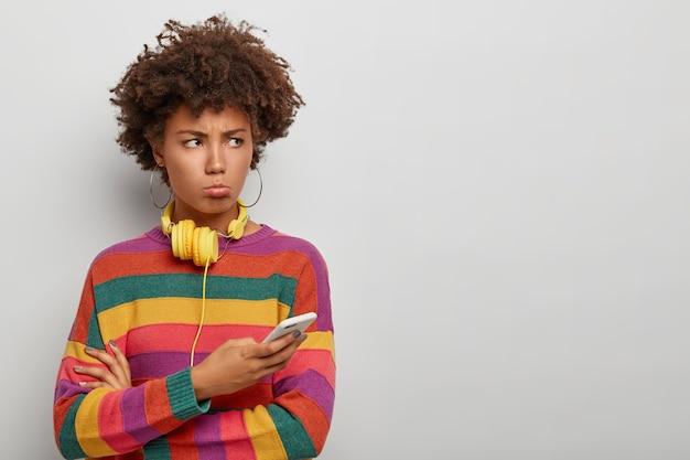 Afro milenar insatisfeita olha com expressão infeliz e ofendida à parte, usa o telefone celular