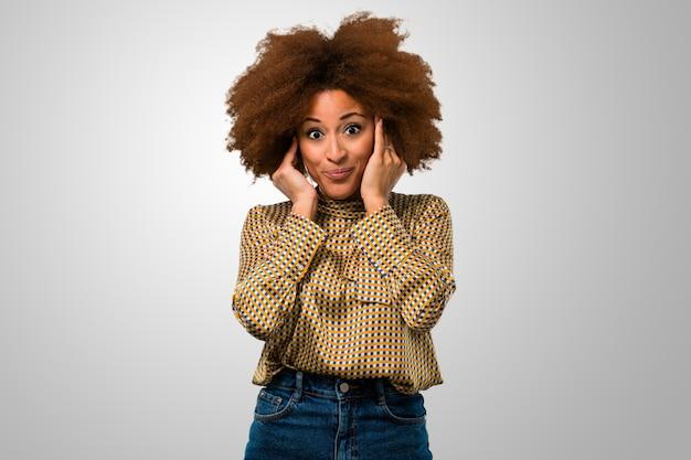 Afro mulher cobrindo as orelhas