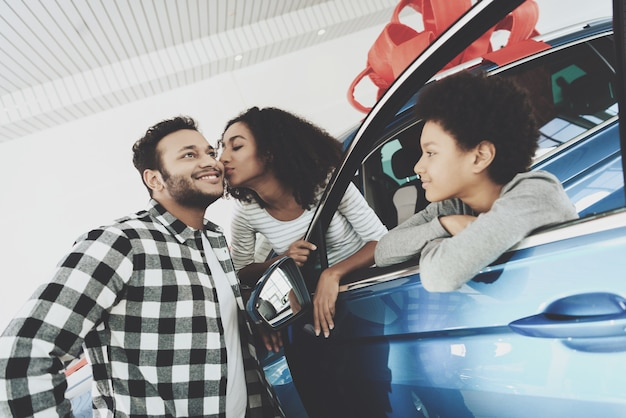 Afro mulher dá beijo ao marido para carro de presente.