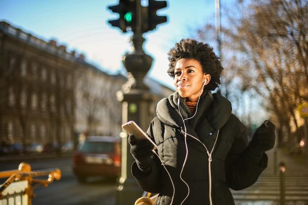 Afro mulher no inverno em uma caminhada