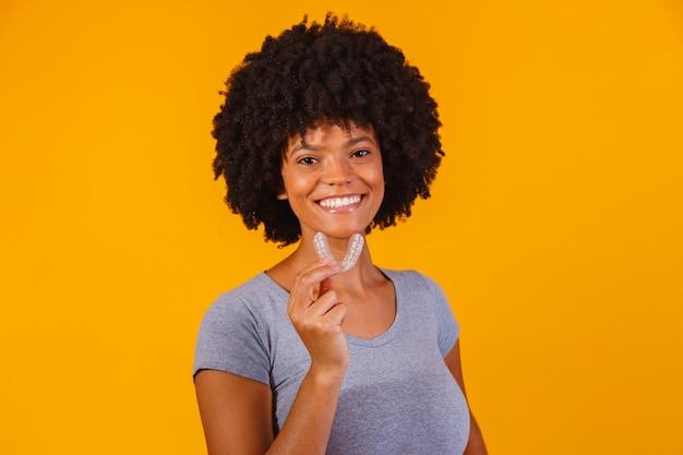 Afro mulher segurando a placa de clareamento. dispositivo invisível.
